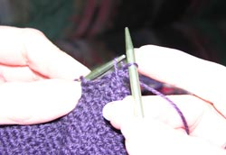 Bring the first stitch forward over the second stitch and over the tip of the right hand knitting needle so that one stitch remains on the right hand knitting needle
