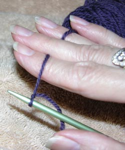 To begin knitting the cast on the yarn is woven between the fingers to create tension on the yarn
