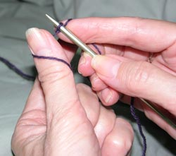 Place the yarn near the knitting needle, around and under the thumb of the left hand