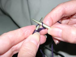 Slip the old stitch off the left needle by pulling the right hand needle to the right.