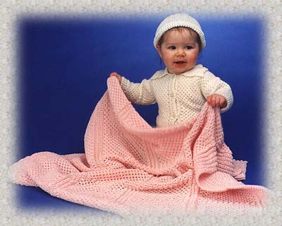 Baby wearing knit tuck cardi and holding knit honeycomb baby blanket