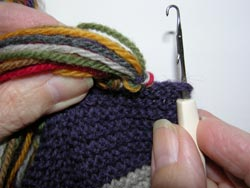 Using a large Latch Tool or Crochet Hook, poke the tool through the scarf edge