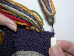 Hook the middle of the 7 strands of yarn with your latch tool or crochet hook