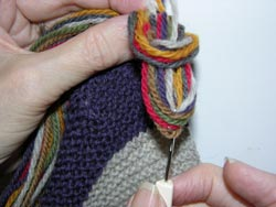 Insert your tool back through the center of the circular loop created in Figure 13 and grab all the yarn ends